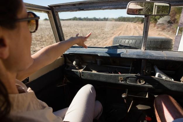 차량으로 여행하는 동안 가리키는 여자