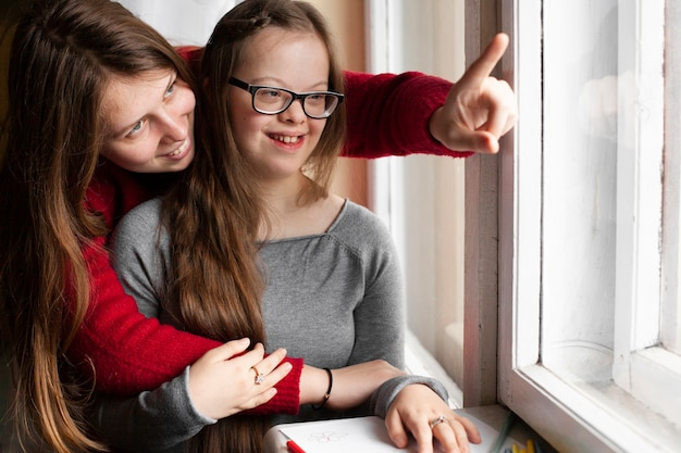 Woman pointing at window to girl with down syndrome