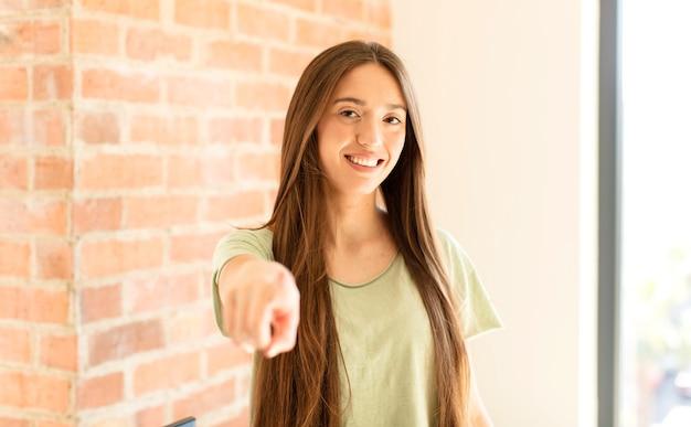 Женщина указывая пальцем, довольная, уверенная, дружелюбная улыбка, выбирая вас