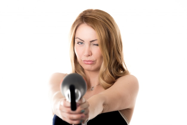 Woman pointing with a hairdryer and one eye close
