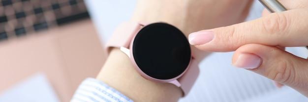 人差し指で時計の文字盤のクローズアップ作業時間の概念を指す女性