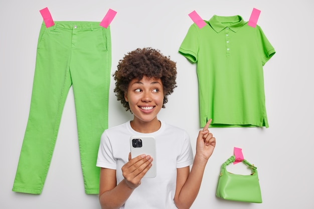 Woman points at casual green t shirt sells unnecessary clothes cleans out wardrobe holds mobile phone makes online shopping advertises items poses indoor