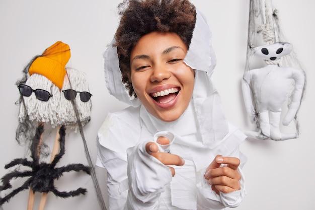 Женщина указывает прямо на камеру собирает аксессуары для карнавала, наслаждается октябрьским временем и жутким праздником, носит костюм призрака, широко улыбается, позирует в помещении на белом