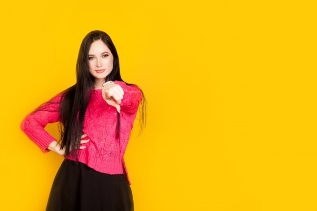 The woman points her finger at you, on a yellow wall, with copy space. concept motivational photos, who if not you, you should make your choice.