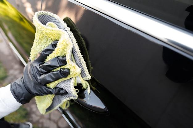 Женщина полирует машину салфеткой из микрофибры и протирает полиролью кузов машины.