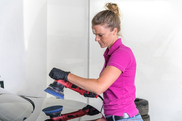 Woman polishing car body in service.