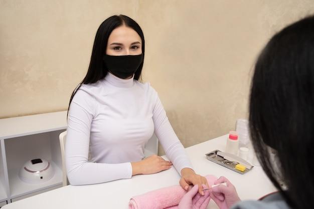 検疫中にサロンで爪を磨く女性。マニキュアネイルペイントヌードピンクカラー。