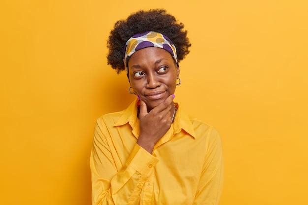 Женщина обдумывает решение держит подбородок, сосредоточенно одетая в повседневную рубашку, думает, как решить проблему, позы снова ярко-желтый