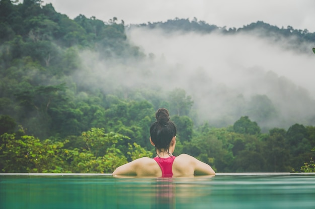 Woman and the pool watching the scene in front of the misty forest