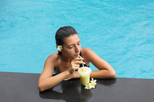 Woman in pool with fruit drink