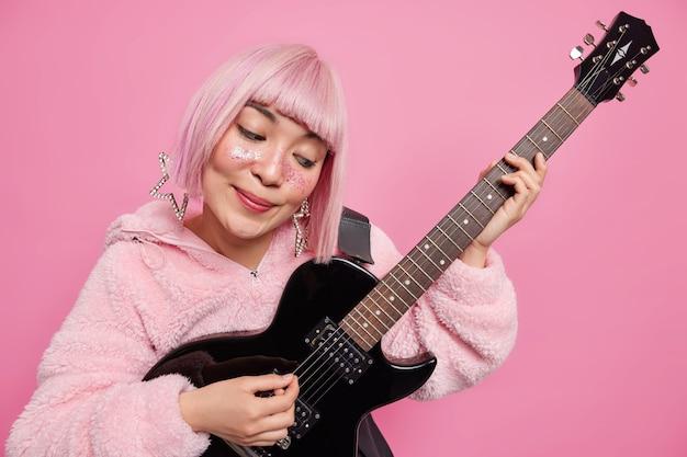 여자 팝 밴드 가수가 어쿠스틱 일렉트릭 기타를 연주하고 세련된 옷을 입는다.