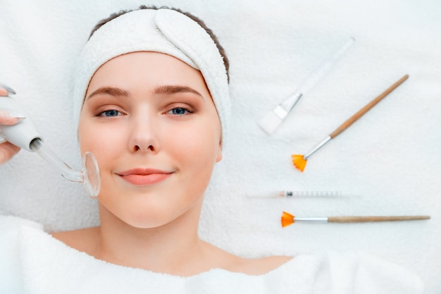 Woman portrait during darsonval cosmetology procedure for skin care lies with beauty injection syringe facial mask brushes cosmetics tool spa devices on white towel beautician in beauty salon