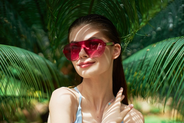 Woman portrait in glasses on a background of green leaves of palm trees, beautiful face