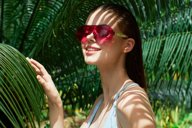 Woman portrait in glasses, green leaves of palm trees, beautiful face