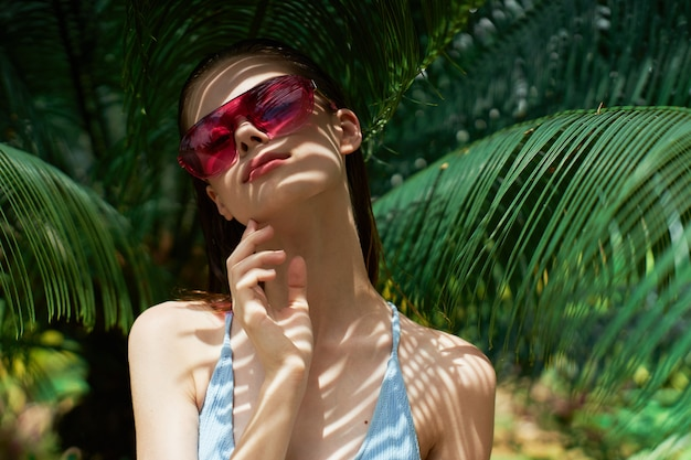 Woman portrait in glasses , green leaves of palm trees, beautiful face