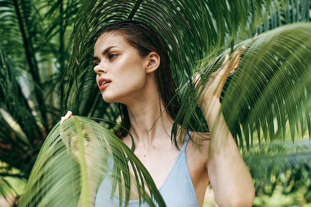 Woman portrait in glasses on a space of green leaves of palm trees, beautiful face