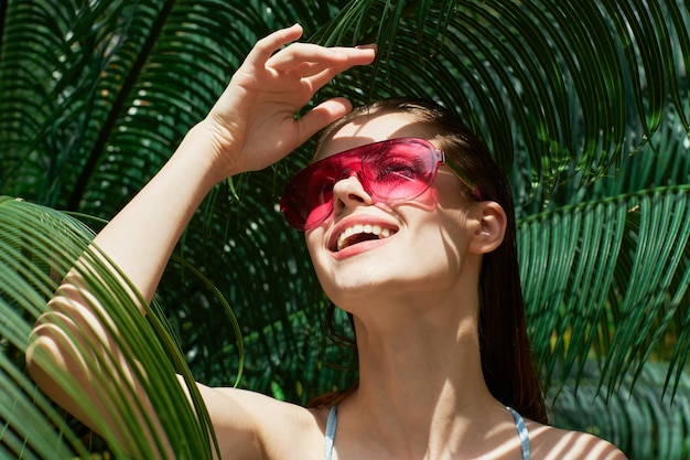 Woman portrait in glasses on a surface of green leaves of palm trees, beautiful face