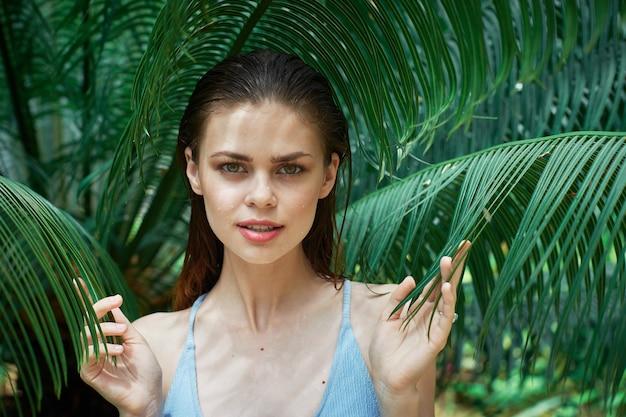 Женский портрет в очках на фоне зеленых листьев пальм, красивое лицо