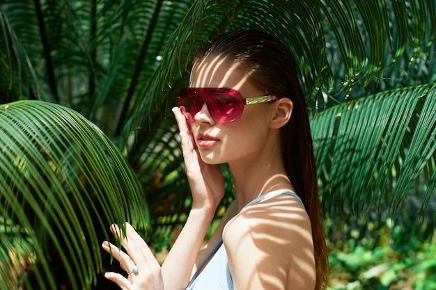 Женский портрет в очках на зеленых листьях пальм, красивое лицо