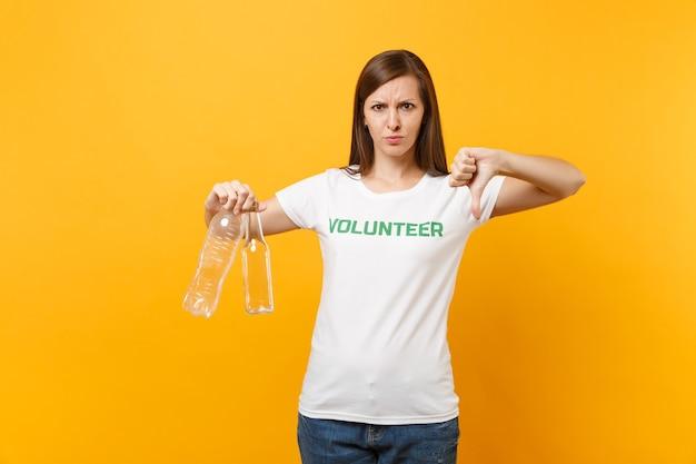 Женский портрет в белой футболке с надписью зеленый заголовок волонтер держит пластиковые и стеклянные бутылки, изолированные на желтом фоне. добровольная бесплатная помощь, концепция работы по сортировке мусора.