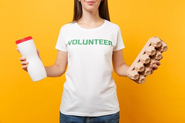 書かれた碑文の緑のタイトルボランティアと白いtシャツの女性の肖像画は、黄色の背景で隔離のプラスチックボトル、段ボール箱を保持します。自主的な無料支援ヘルプ、ごみの分別の概念。