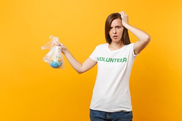 白いtシャツで書かれた碑文の緑のタイトルのボランティアの女性の肖像画は、黄色の背景で隔離のビニール袋地球世界の地球に保持します。自発的な無料支援ヘルプ、チャリティーグレイスコンセプト。