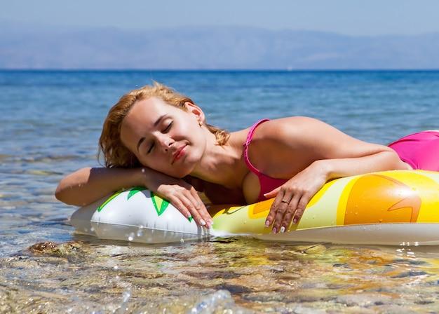 노란색 ananas 수영 반지와 함께 해변에 누워 여자 초상화