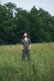 自然の上の女性の肖像画は、緑の木々の散歩を背景に彼のポケットに手を握ります