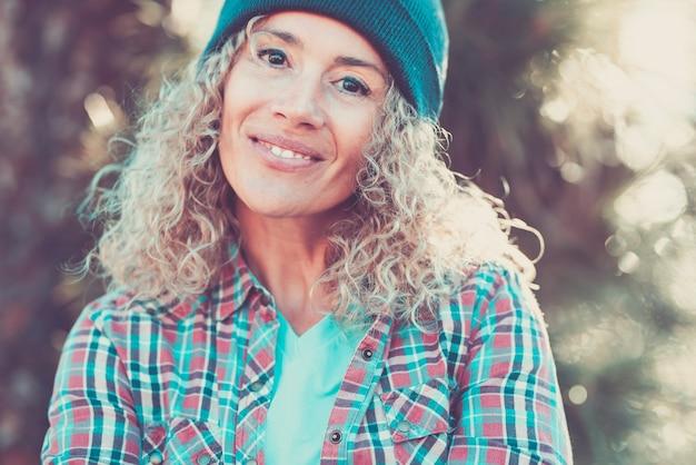 屋外の女性の肖像画-陽気な白人女性の人々は笑顔でカメラを見て楽しんでいます-自然な屋外の焦点がぼけたボケ味の背景-幸せな中年女性のヒップスタースタイル