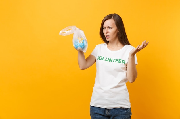 Woman portrait in white t-shirt written inscription green title volunteer hold in plastic bag earth world globe isolated on yellow background. voluntary free assistance help, charity grace concept.