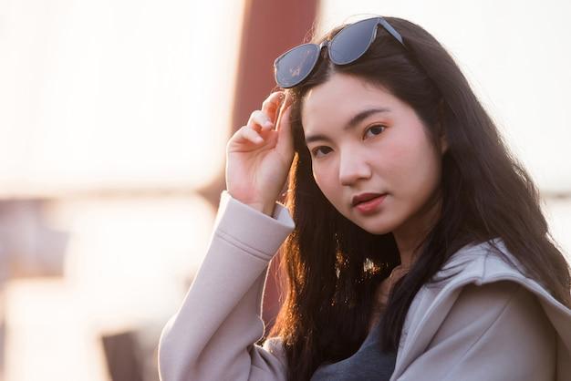 夕方に買い物をする女性の肖像画の若いタイの女性、川沿いの夕日を歩く女性のライフスタイル、率直な肖像画の女性バンコク、タイ、アジア。
