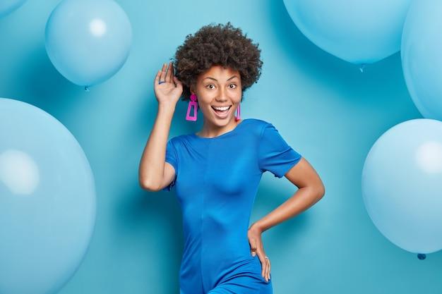ファッショナブルなドレスを着た女性は笑顔で積極的に青にお祝いムードのポーズをとっている