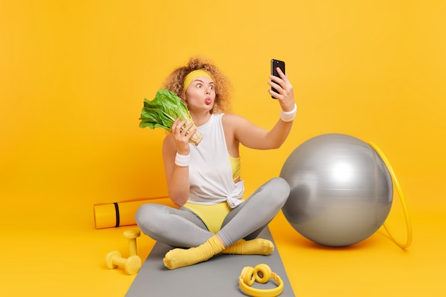 Woman poses for making selfie keeps lips folded holds mobile phone eats healthy vegetables keeps to diet sits on mat surrounded by sport equipment