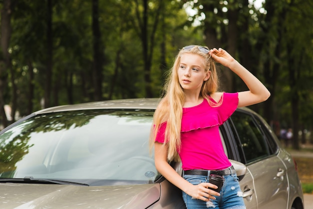 Woman poses near car with glasses and cup
