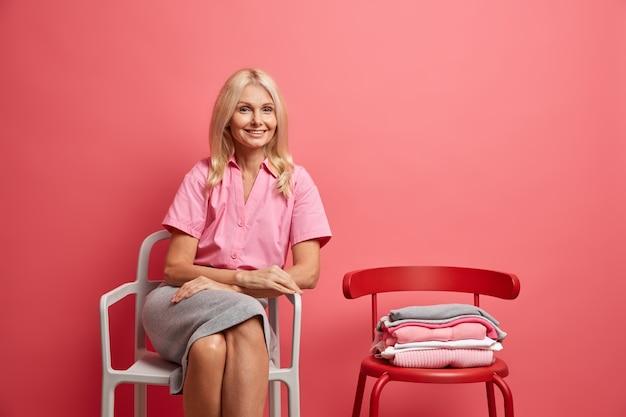 여자는 분홍색에 고립 된 블라우스와 치마를 입고 접힌 옷으로 편안한 의자에 포즈