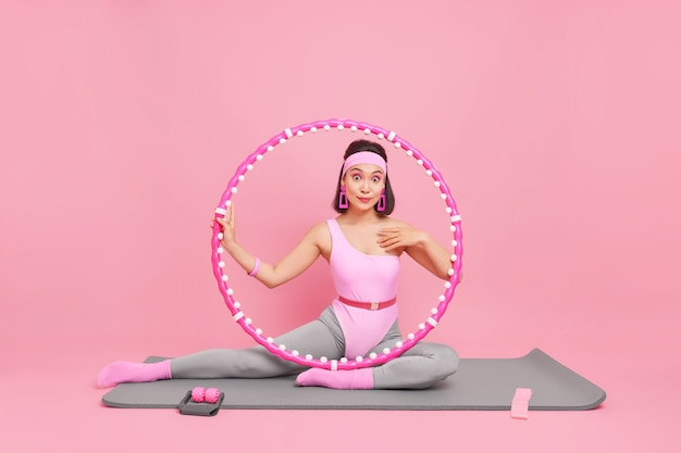 フラフープやその他のスポーツ用品を備えたフィットネスマットでポーズをとる女性は、自宅でスポーツトレーニングを行っています