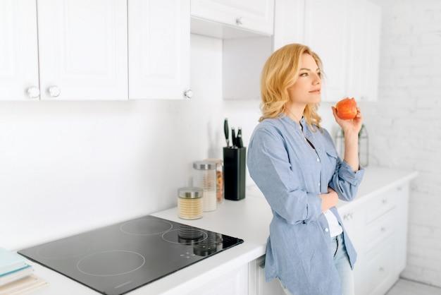 Женщина позирует на кухне с белоснежным интерьером