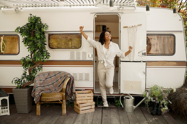 Woman poses at the rv entrance, camping in a trailer. couple travels on van, vacations on motorhome, camper leisures in camping-car