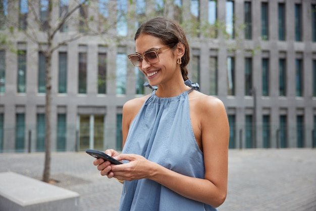 Woman poses in urban setting during sunny day wears sunglasses blue dress uses smartphone gadget for communication chats online uses navigator to find route