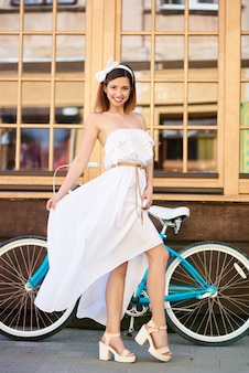 Woman posing against a vintage bicycle and wall with big windows.