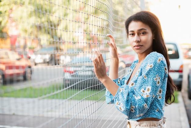 女性がポーズし、有線フェンスに彼女の手を保つ