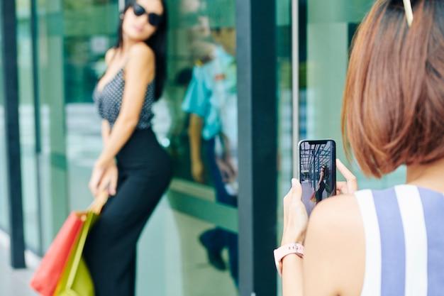 女性が電話のカメラでポーズ