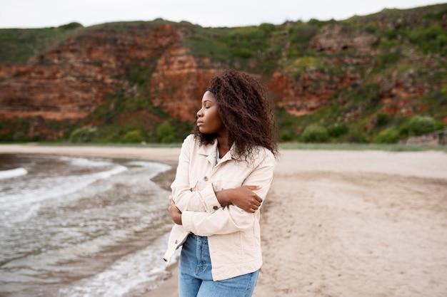 海辺のミディアムショットでポーズをとる女性