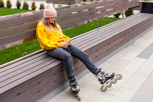 Woman posing on bench while wearing roller blades