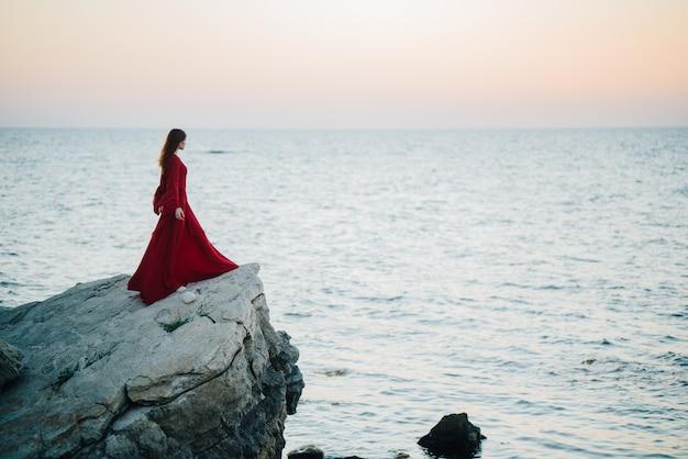 Женщина позирует у океана