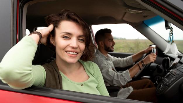 Donna che posa in macchina vicino al ragazzo