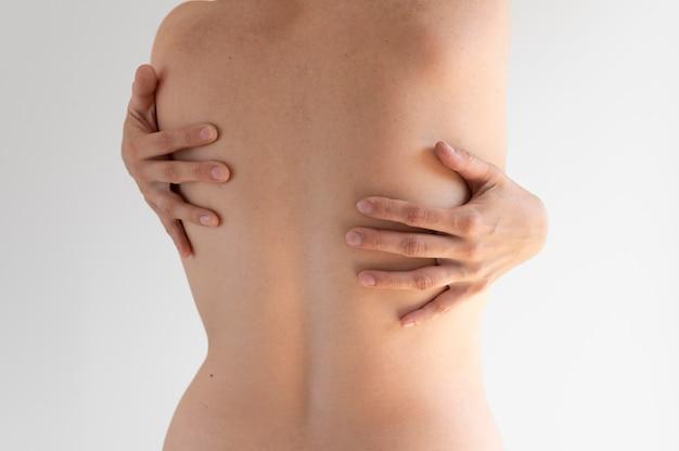 Donna che posa con sicurezza nuda e mostra le spalle