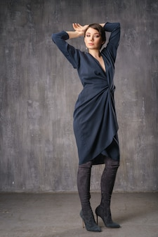 Woman posing in fashionable clothing in the studio in the background