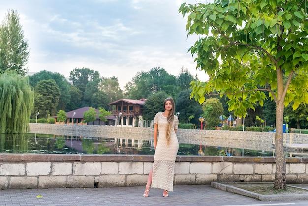 近代都市の湖の前でドレスを着てポーズをとる女性