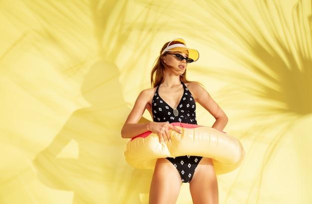 여자 유행 bodysuit 및 분홍색 도넛 포즈